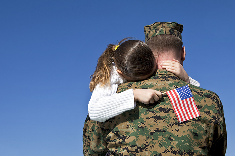 Dad in Military with daughter hugging him as he says goodbye